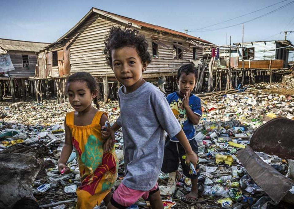 Children play in a rubbish dump in Hanuabada village, Port Moresby, Papua New Guinea. There is no running water and proper toilets in people's homes. 30 May, 2013. © Vlad Sokhin