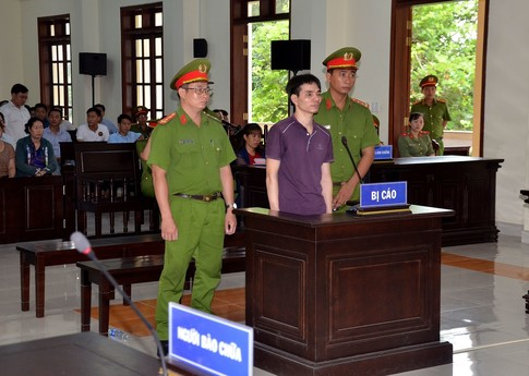 environmental activist Nguyen Ngoc Anh (C) standing in a courtroom during his trial in southern Vietnam's Ben Tre province